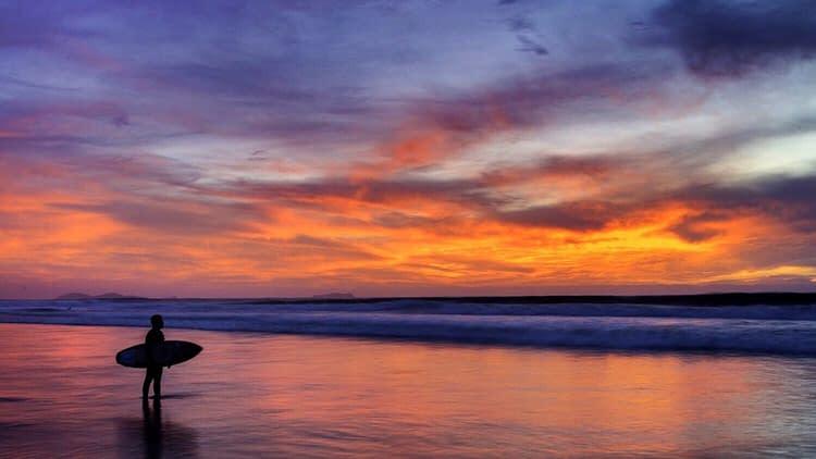 Oranger Sonnenuntergang am Meer mit Surfer